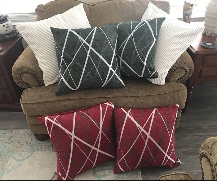 A set of red throw pillows with a modern white/grey design and a set of grey throw pillows with a white/grey modern design