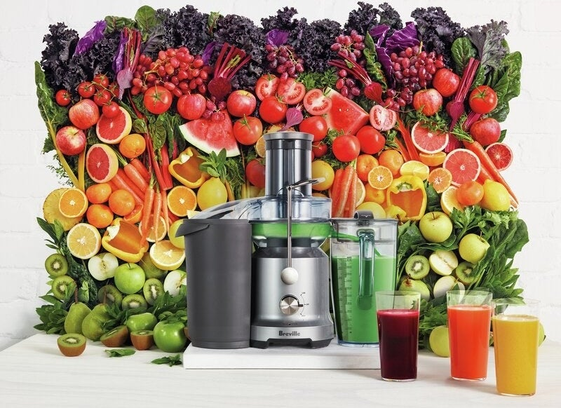 the juicer surrounded by a rainbow of fruits and vegetables