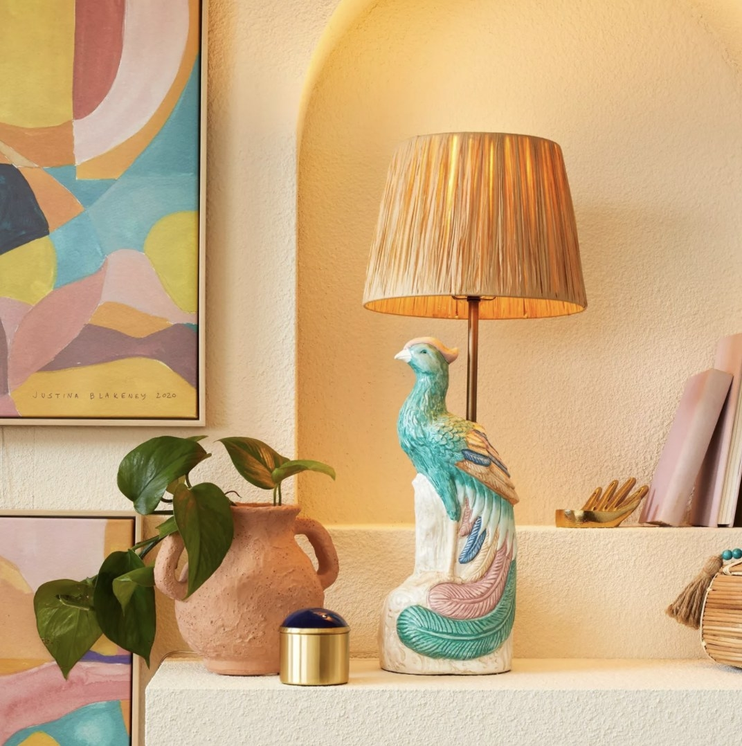 The peacock lamp has light teal, dark blue, pink and yellow coloring