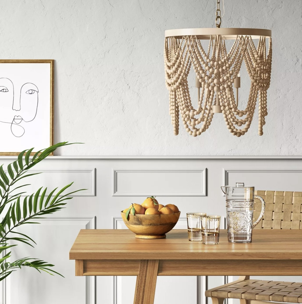 The large tan wooden bead chandelier is hung above the table