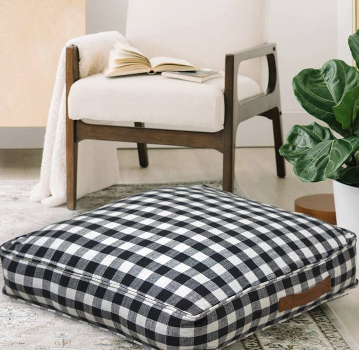The black gingham floor pillow has a brown handle