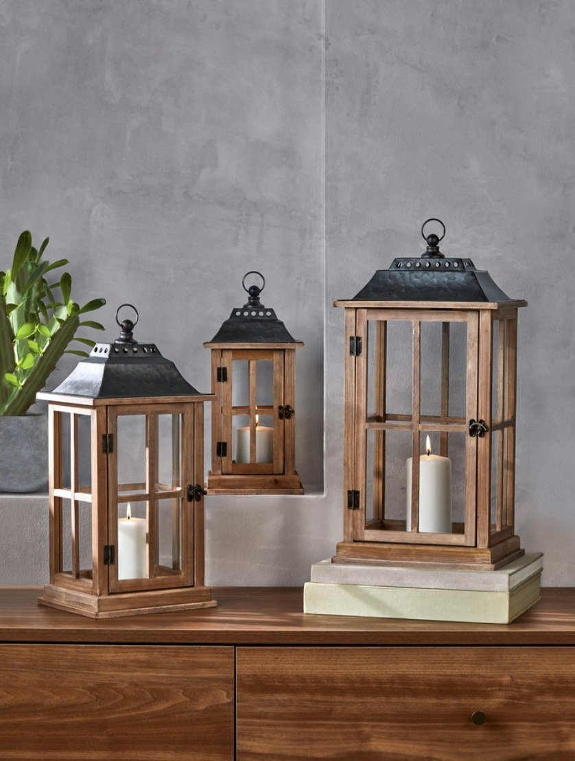 The wooden lantern has a dark iron top and black fixtures