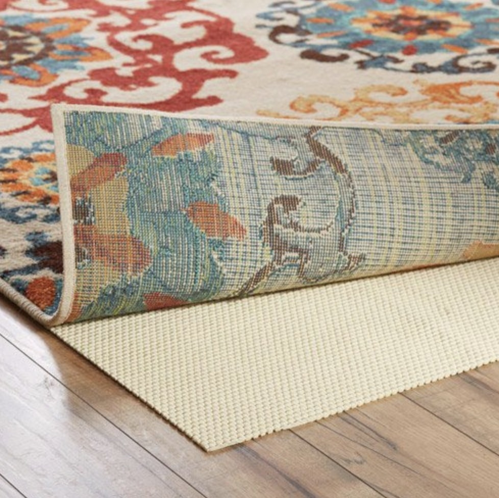 The cream colored cushion is underneath a multi-colored pattern rug