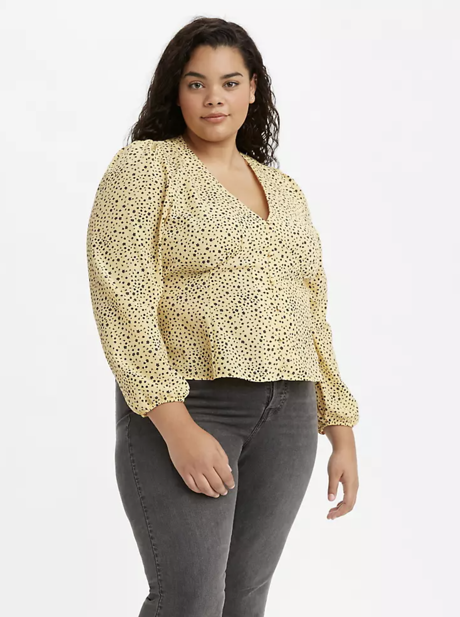 Model in yellow v-neck puff long-sleeved blouse with small black polka dots