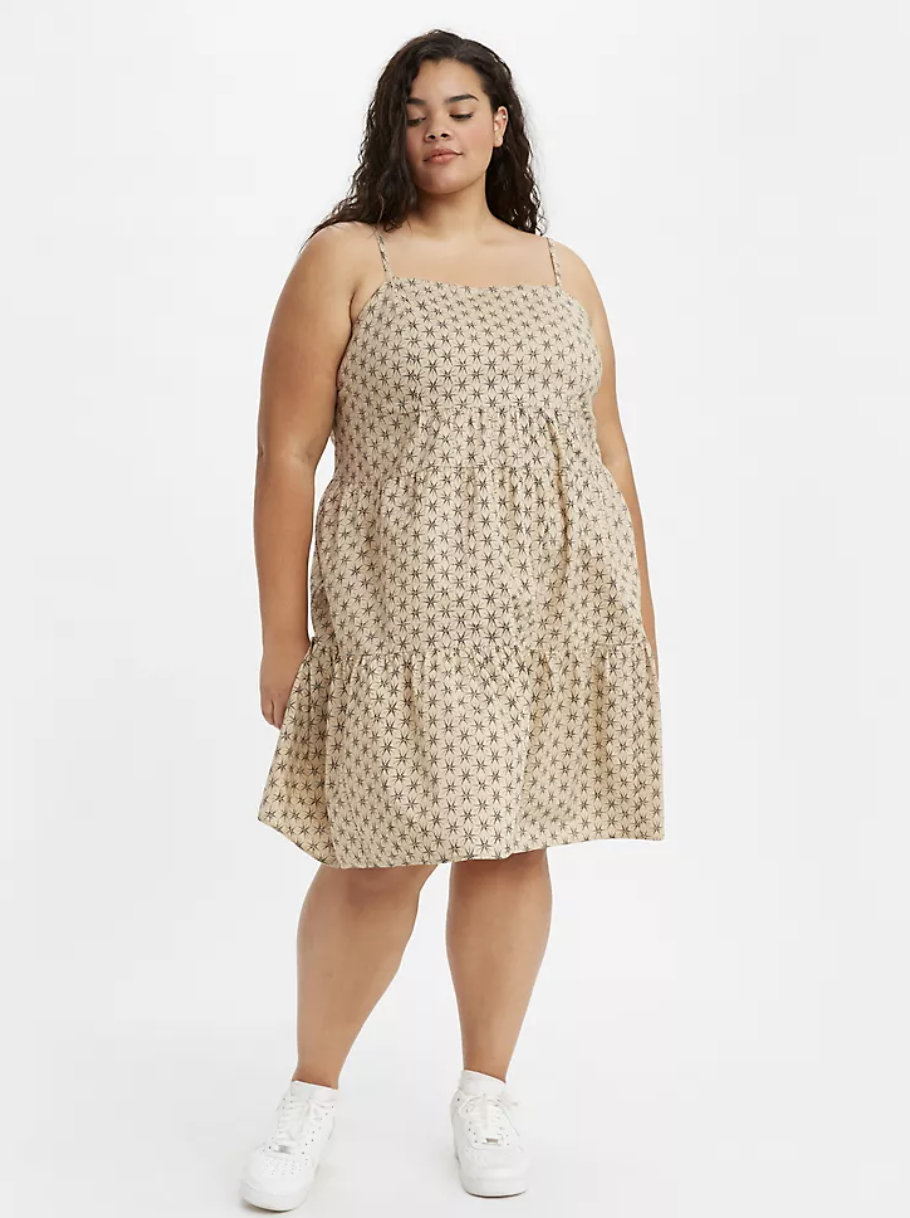 Model in a strappy tiered midi dress in a pale yellow with gold star patterns
