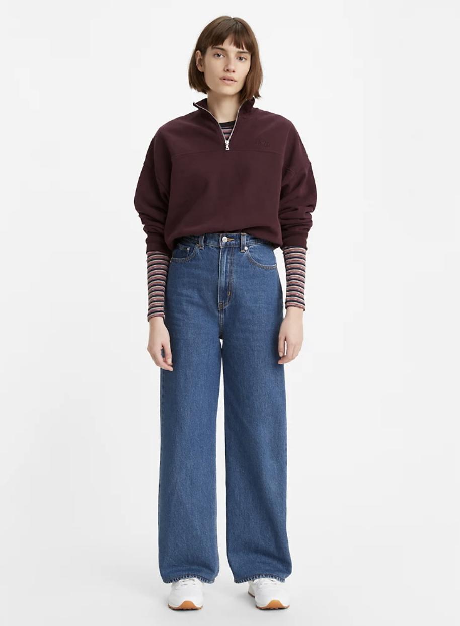 Model in high waisted medium denim wide leg jeans