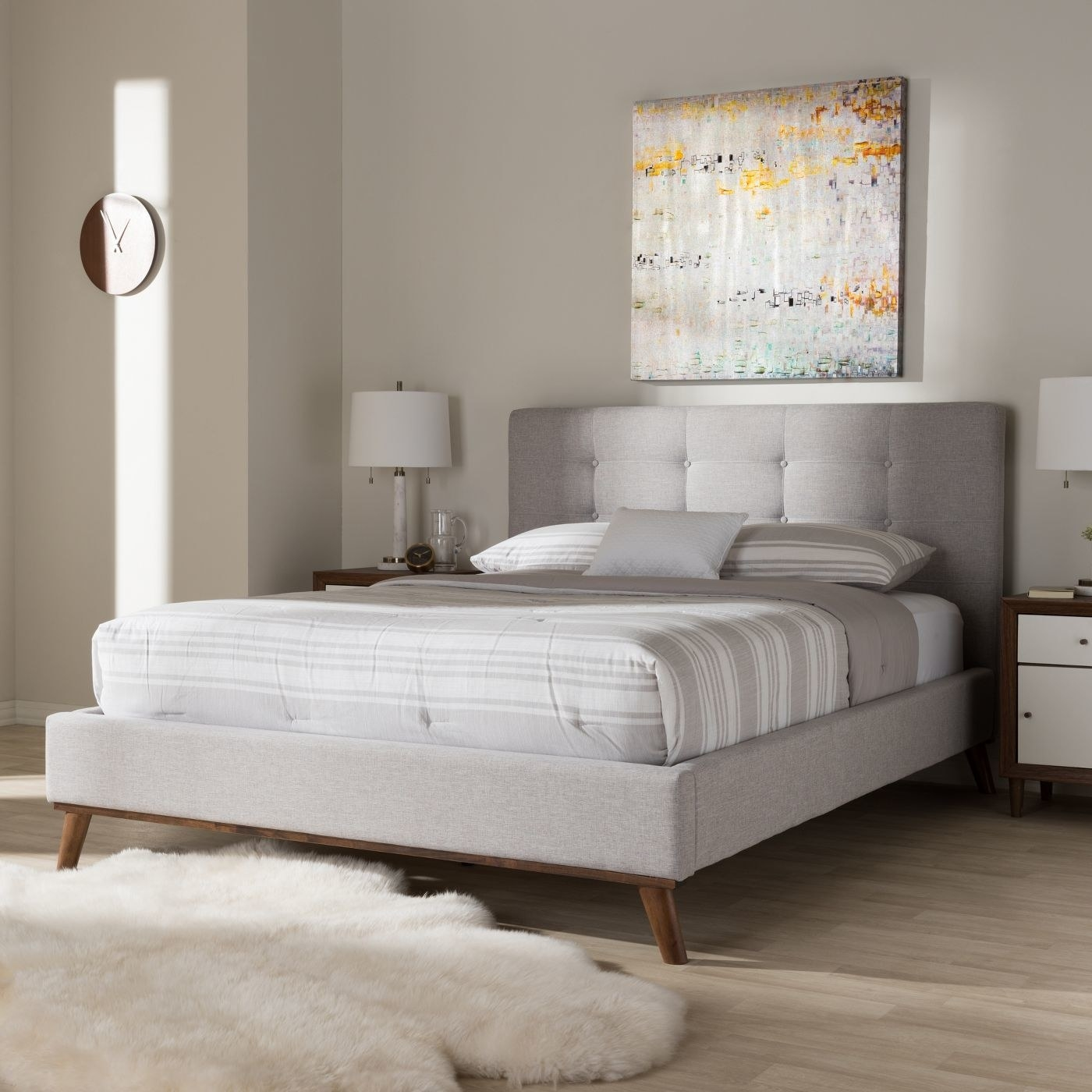 grey upholstered platform bed with wooden legs