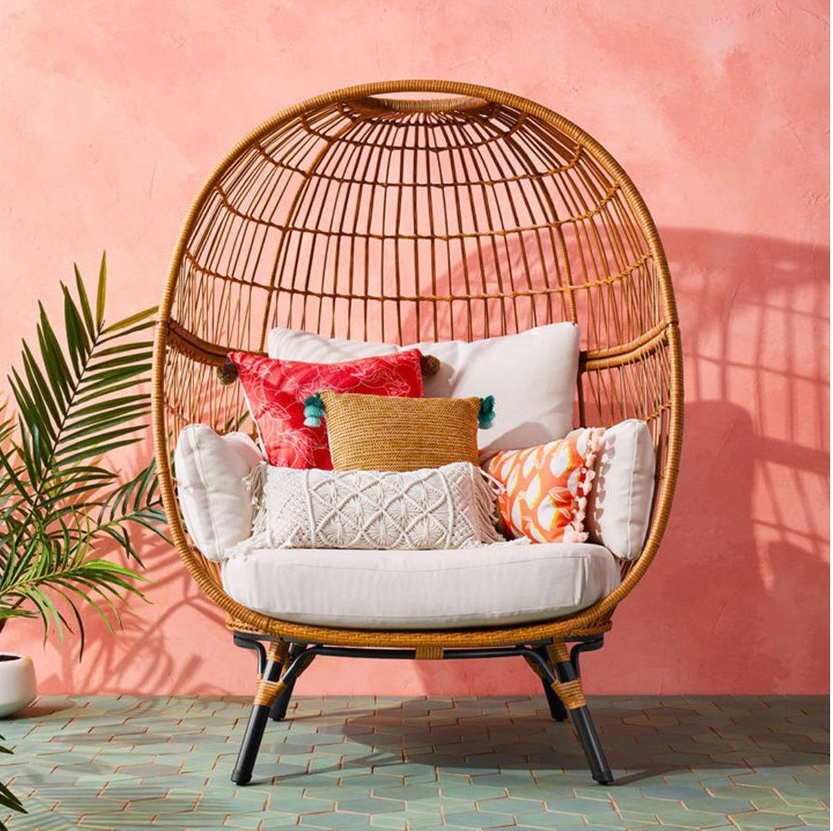big wicker egg chair with white cushions and colorful throw pillows