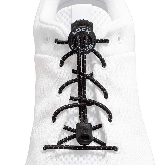 A white shoe with black elastic laces on it