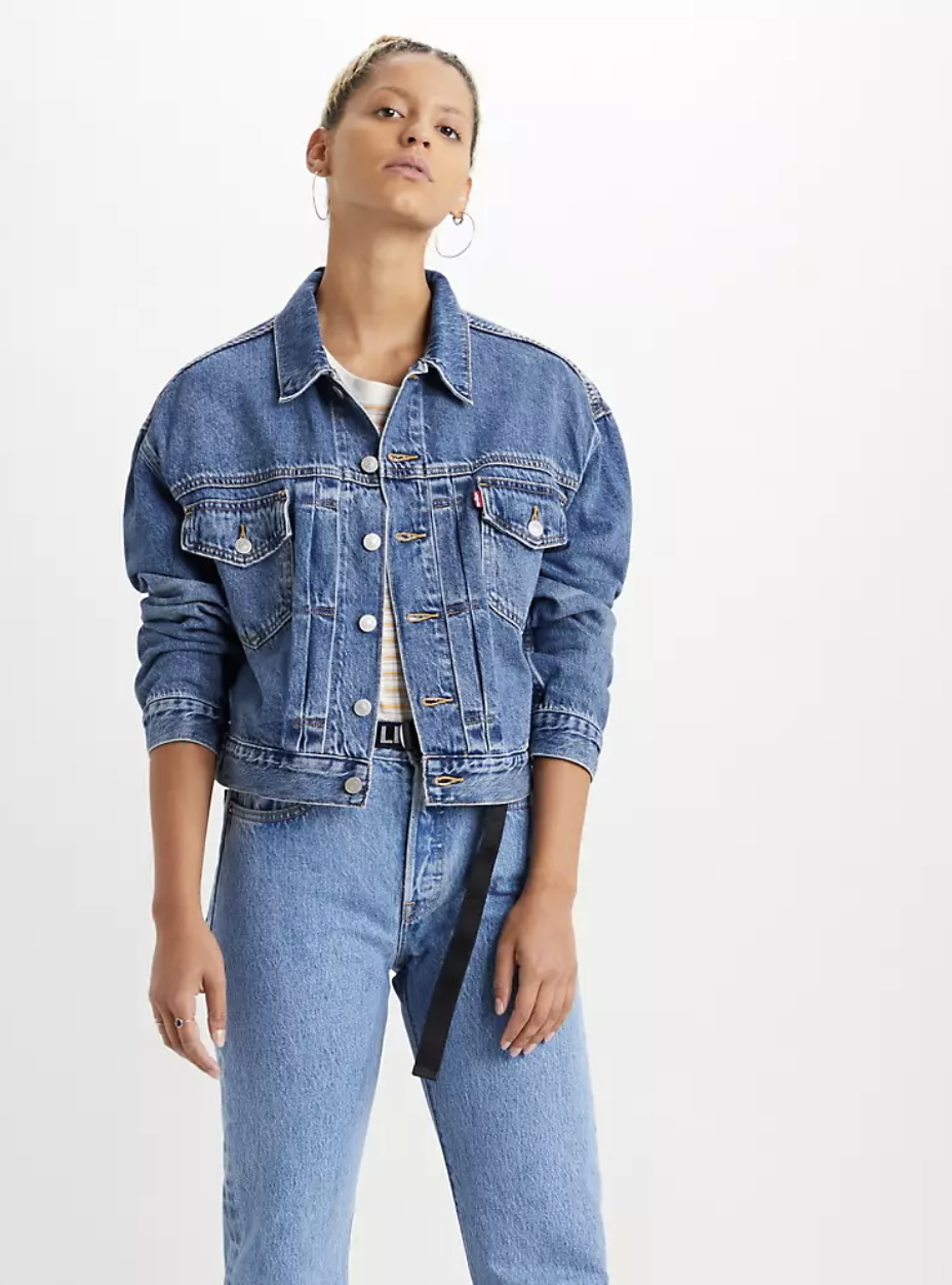 Model in collared medium denim trucker jacket with front pockets and side pockets