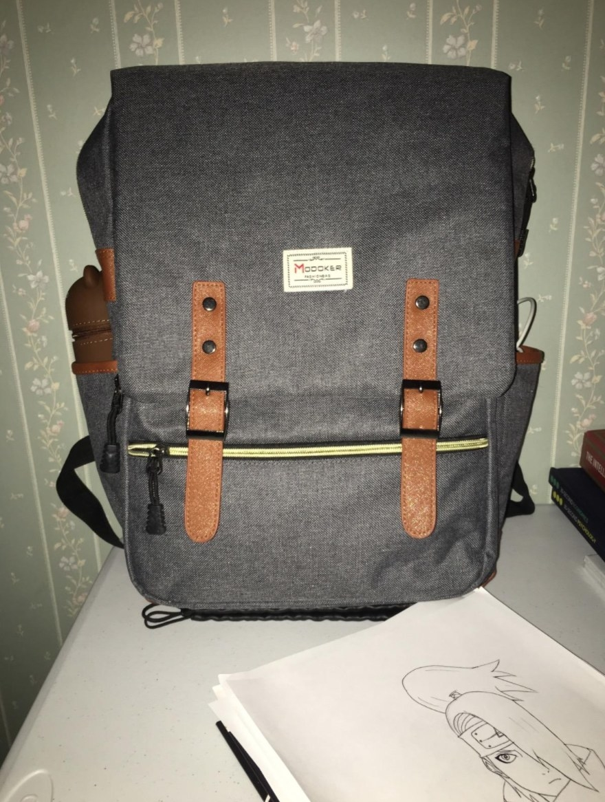 the backpack in gray with brown straps