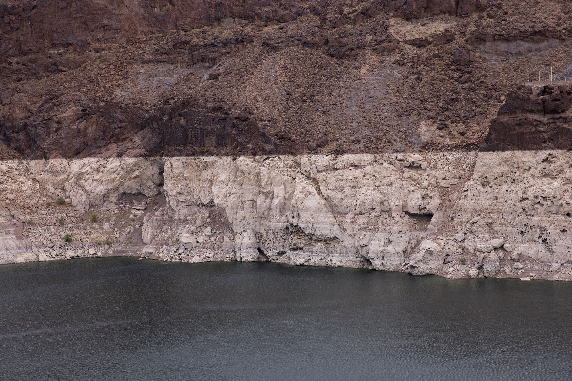 Dropped water levels reveal a lighter shade of rock in a dam
