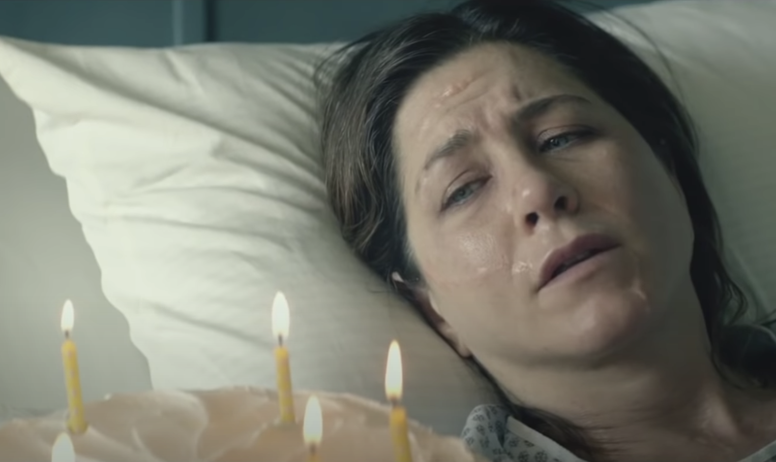 Jennifer aniston sweating miserably in a hospital bed and looking at a birthday cake in cake