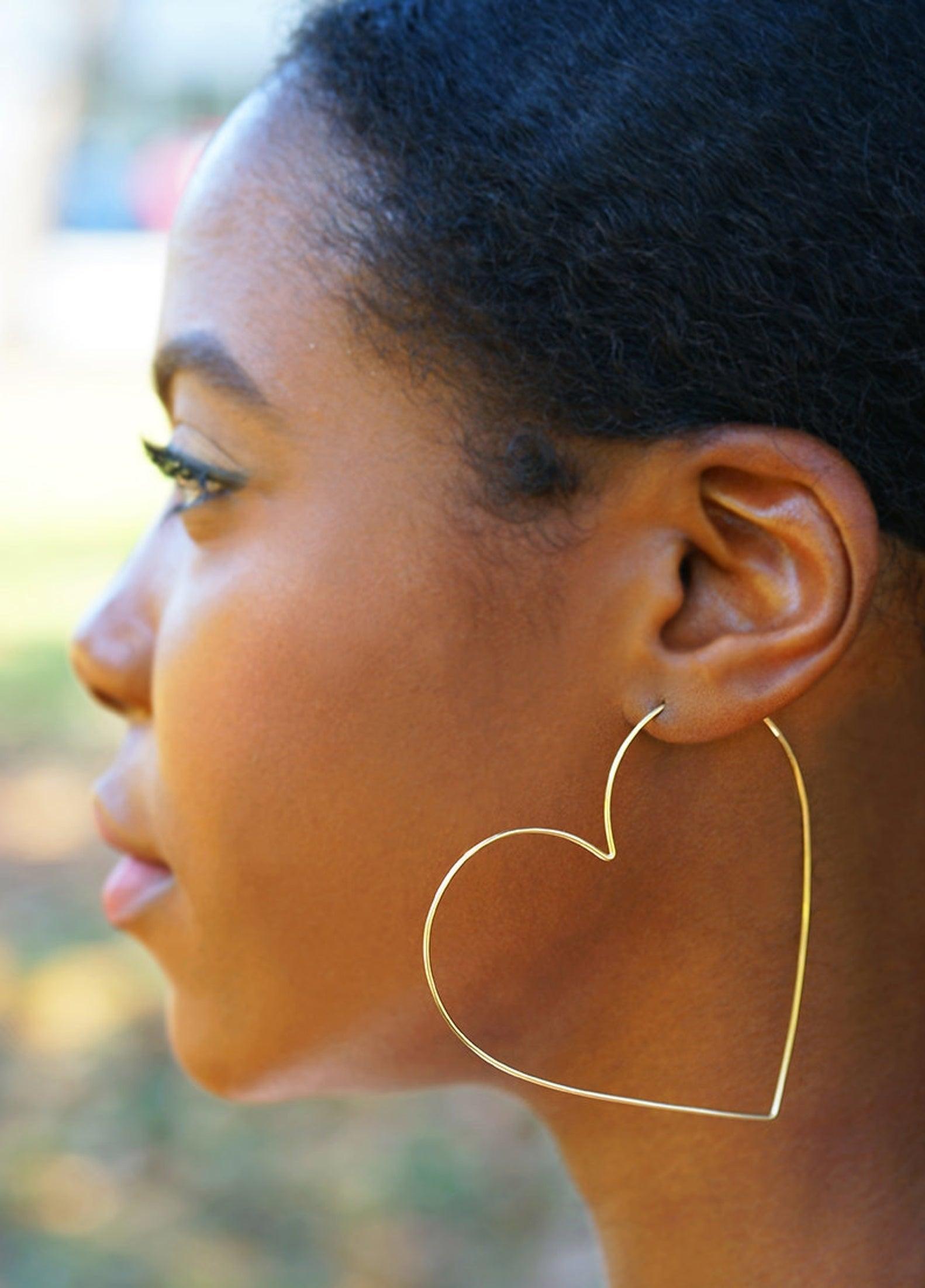 model wearing heart-shaped hoop earrings