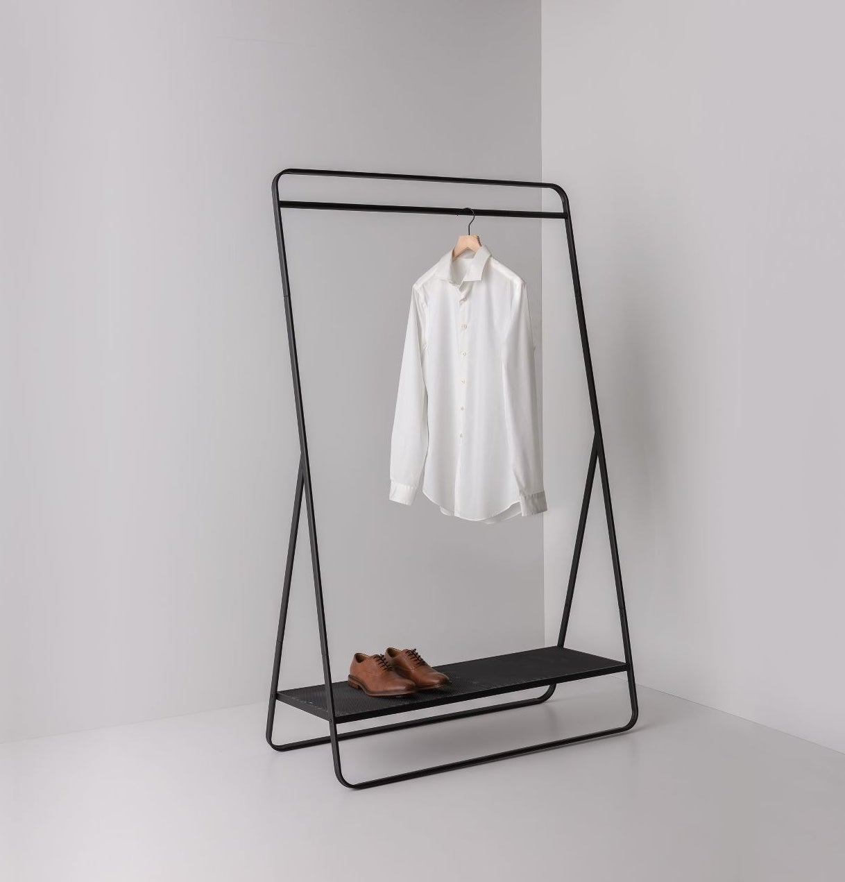 metal garment rack with a shirt hanging and shoes on the bottom shelf