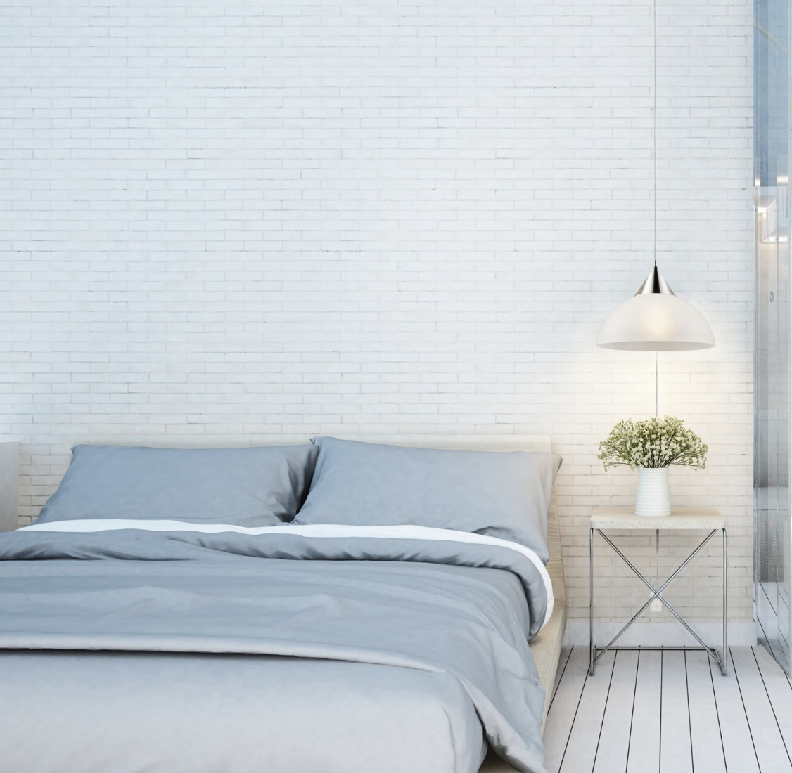 The white dome light has silver accents is next to a white brick wall and blue bedding