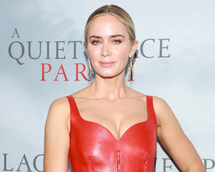 Emily softly smiles while wearing a red leather dress