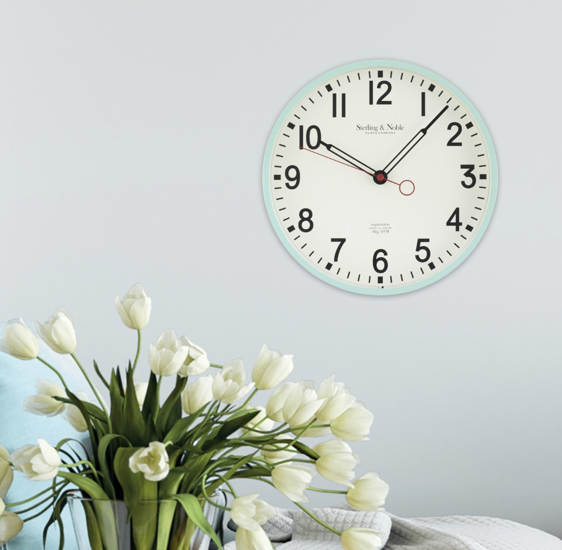 The mint clock is on a bright wall and has black minute hands and red seconds hand