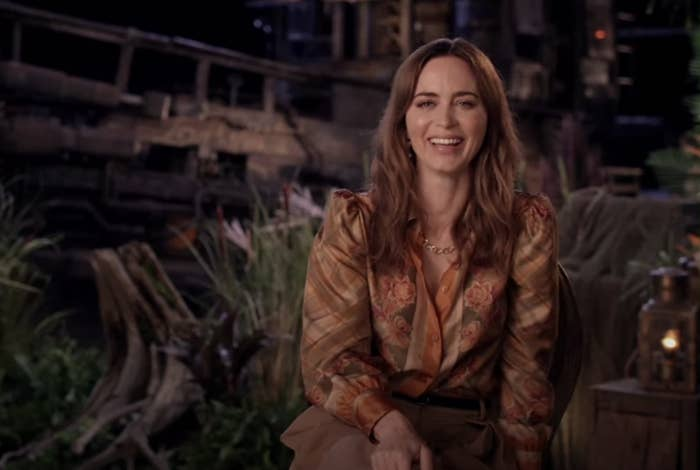 Emily laughs while doing the interview in front of a jungle backdrop from the movie