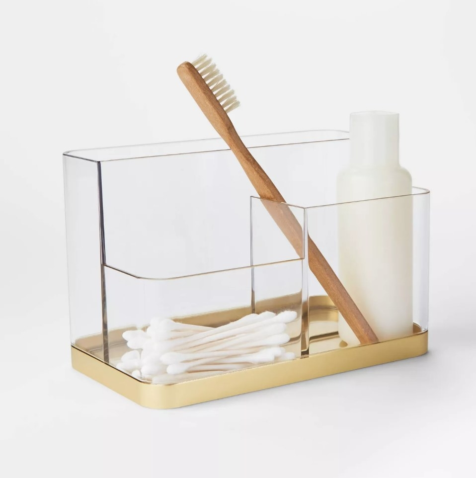 Vanity tray with gold bottom tray filled with cotton swabs, tooth brush and lotion