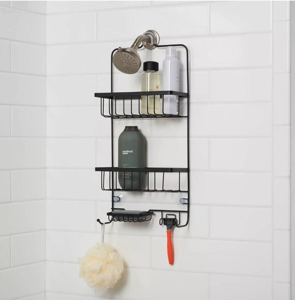 The black shower caddy against white tile with razor, sponge, and bottles inside