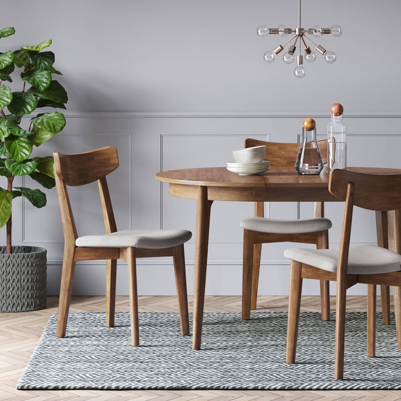 wood rounded dining table with chairs around it