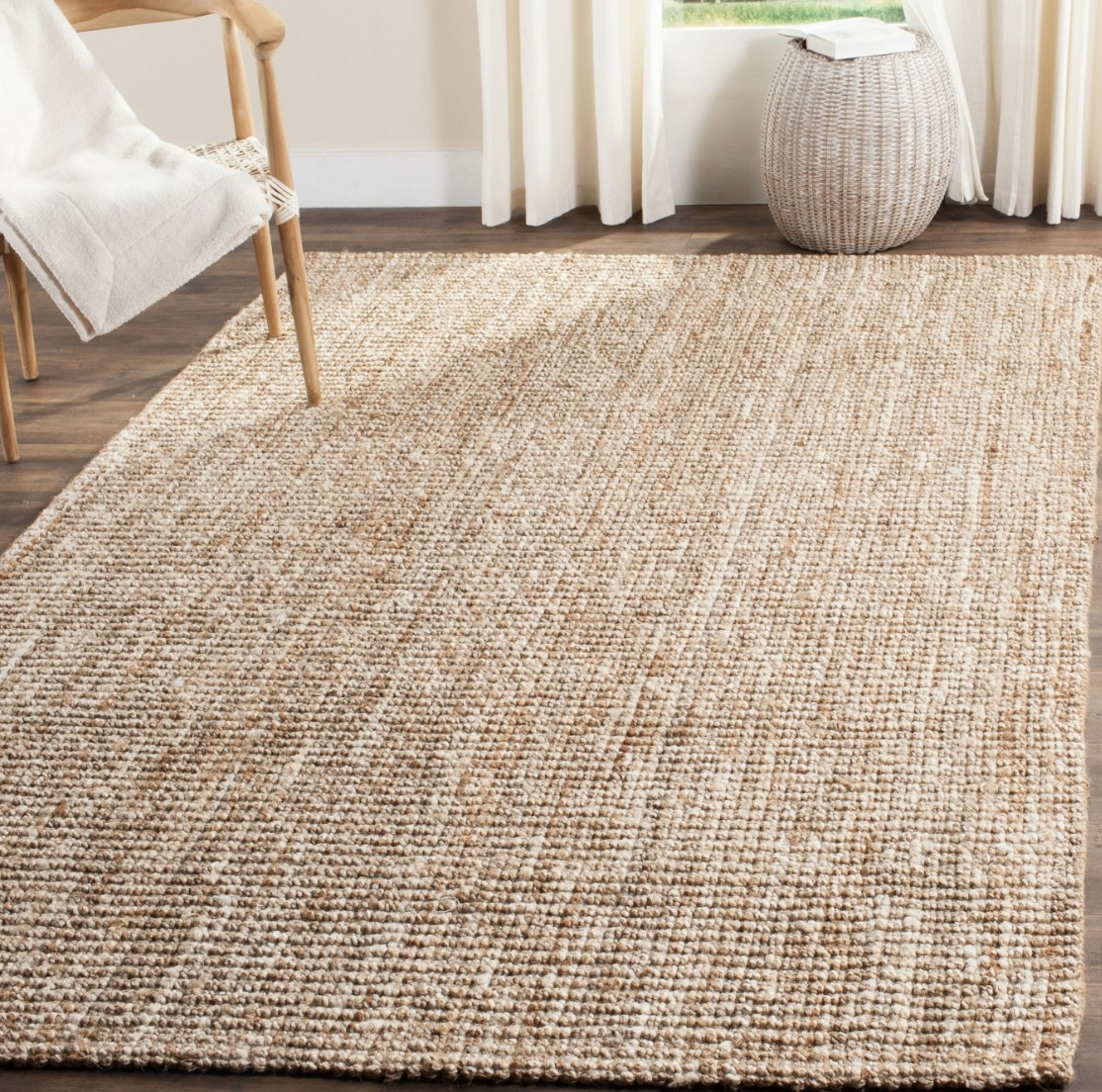 The natural colored loom rug is on a dark brown wooden floor