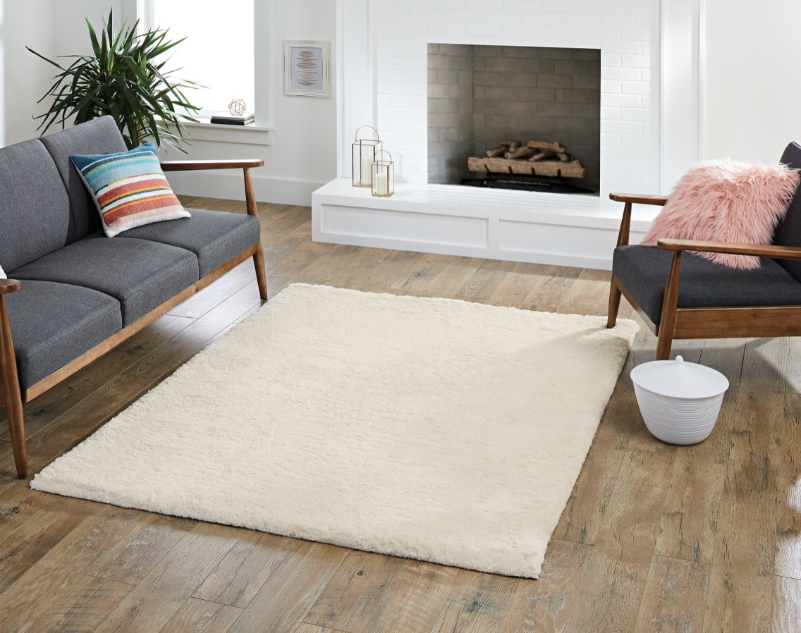 The white plush rug is on a wooden floor and surrounded by furniture