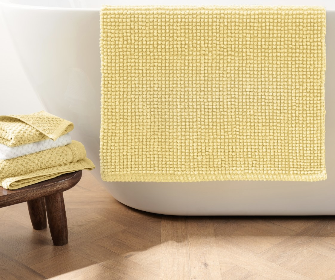 The yellow popcorn rug is hung over the side of a white bathtub
