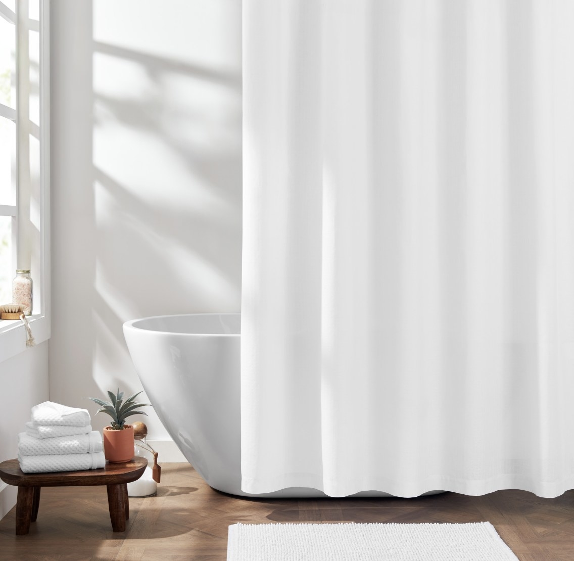The white curtain is in a natural and bright bathroom