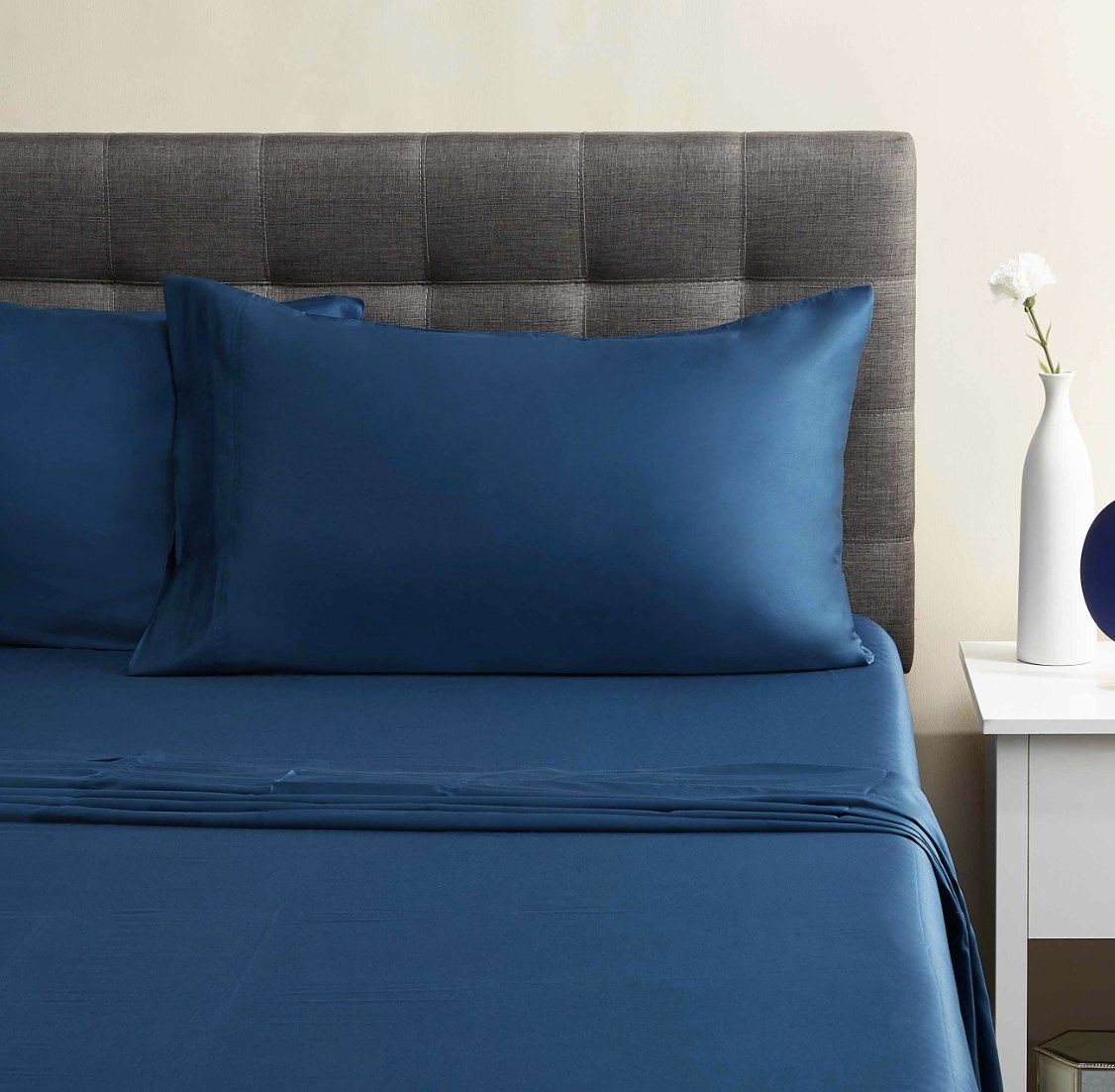 The baltic sea blue sheet set is over a made bed with two pillows