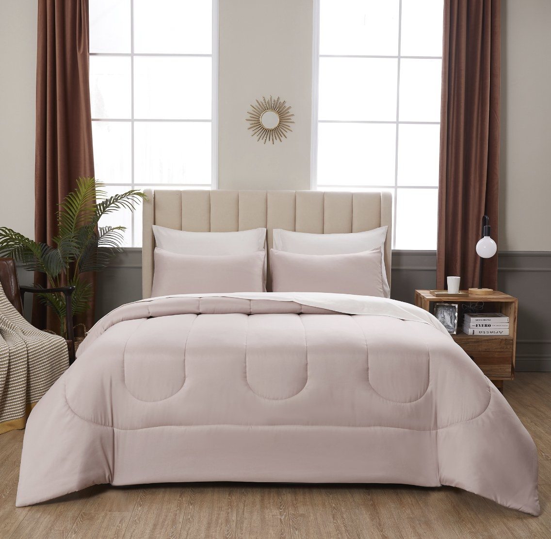 The blush colored set is on a made bed and is in a neutral-toned and well lit room