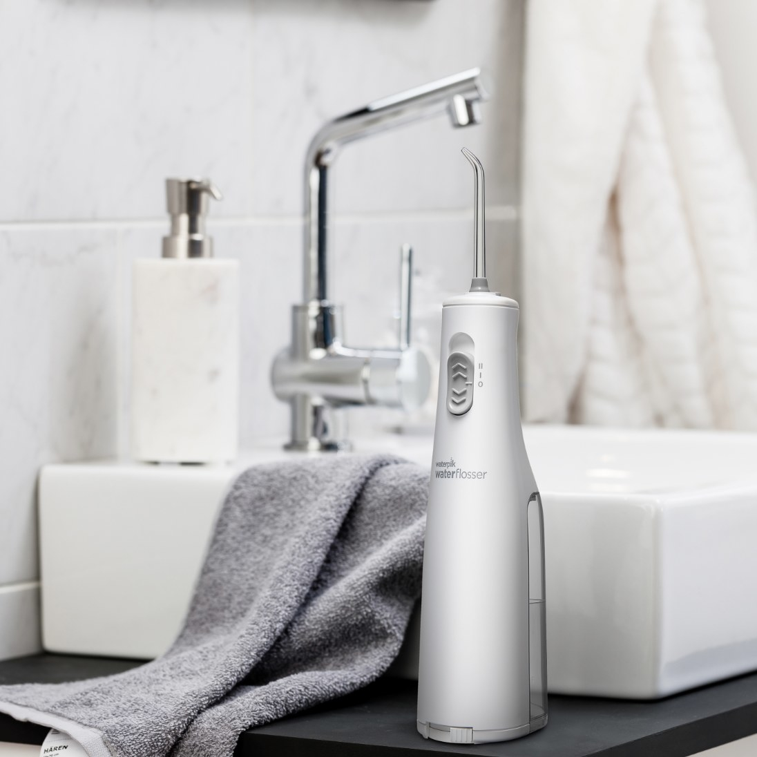 The white flosser is next to a white sink with silver touches