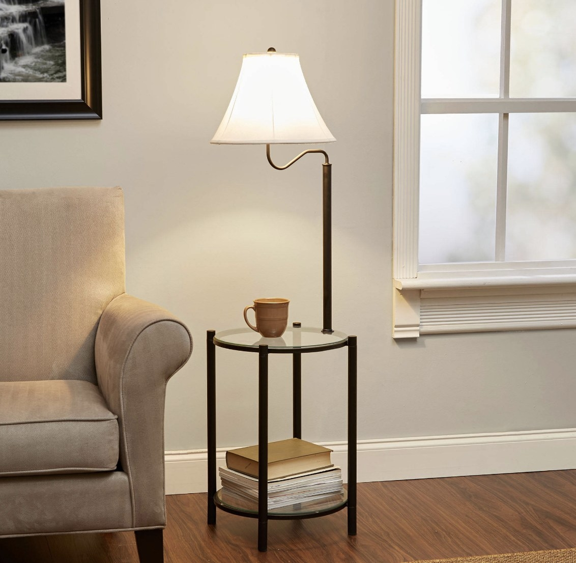 The black side table has clear panels and a black framed lamp with a white shade