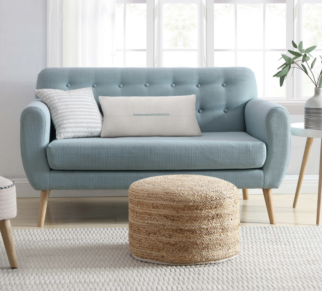 The jute pouf is in front of a light blue couch