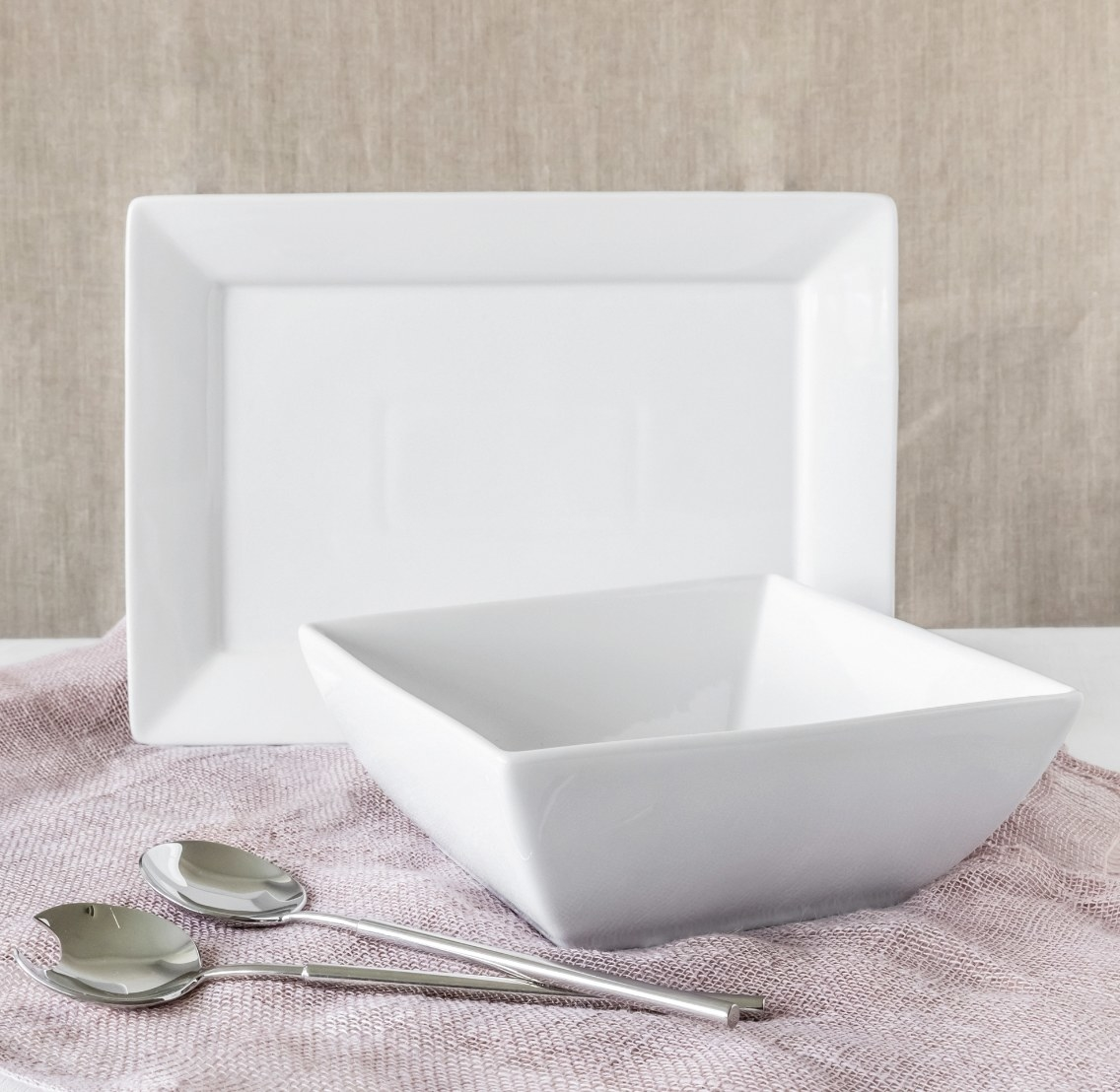 The white square bowl and plate with two silver spoons