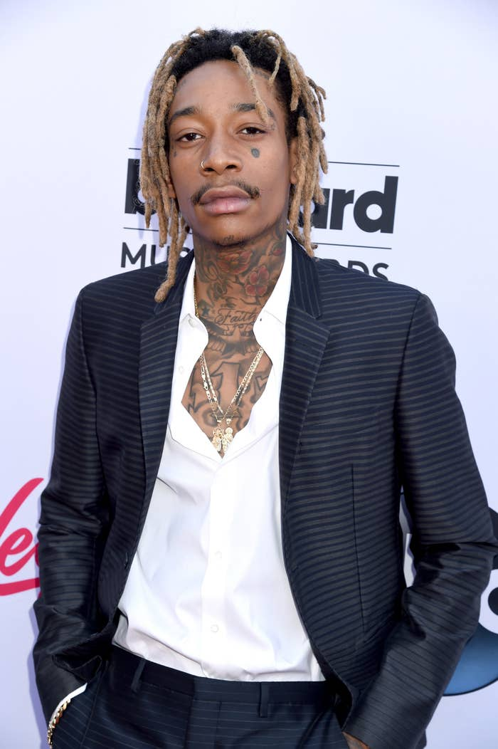 Wiz Khalifa poses for the camera with his hands in his pockets while wearing a suit and button-down shirt