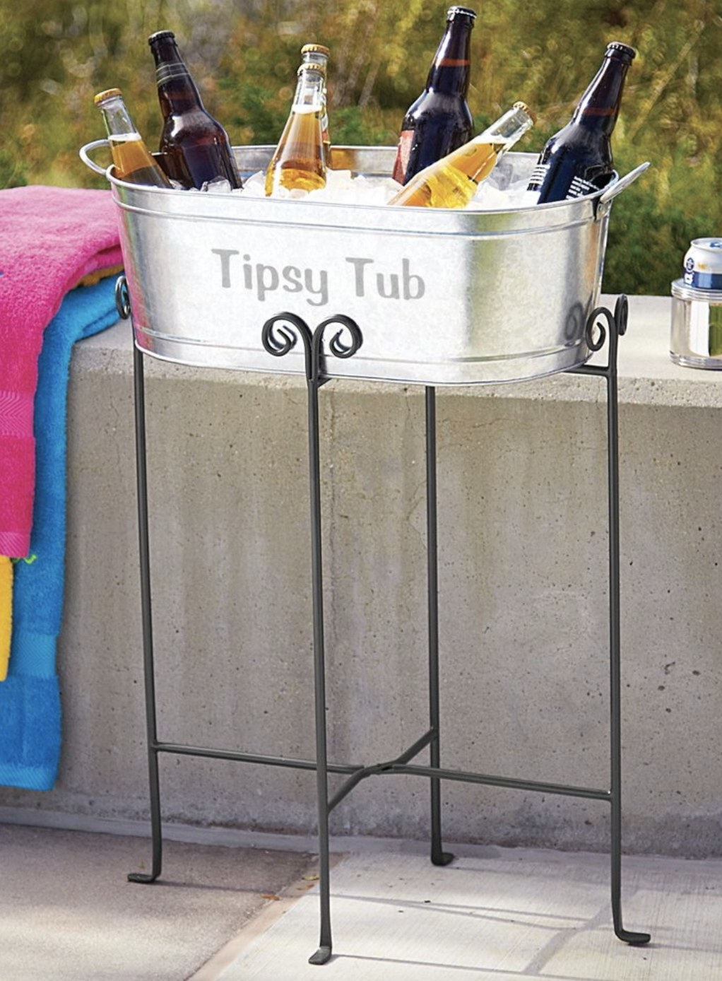 """The silver tub says """"Tipsy Tub"""", has ice, is holding drinks and is atop a black iron stand"""