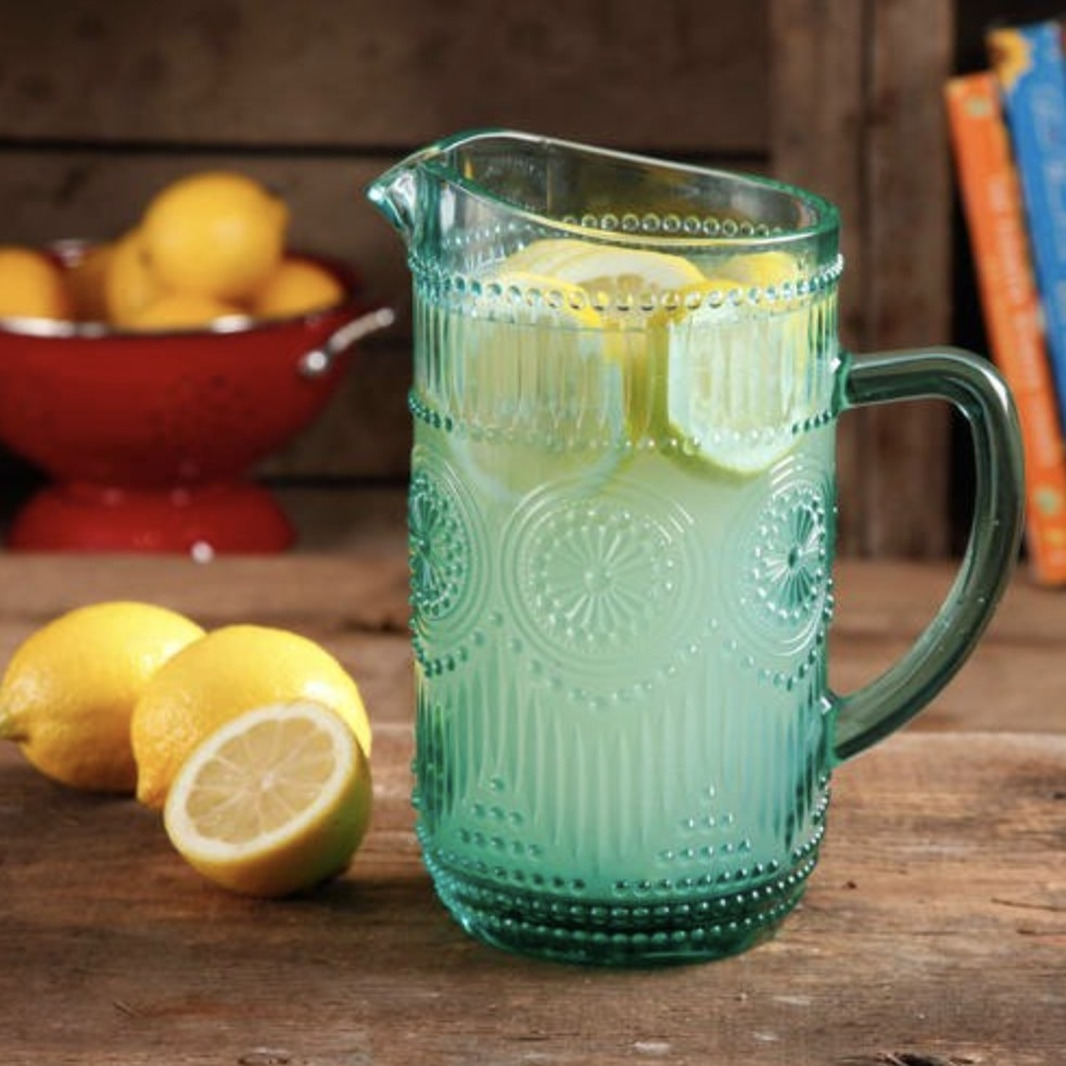 The turquoise glass pitcher is holding lemonade and slices of lemonade