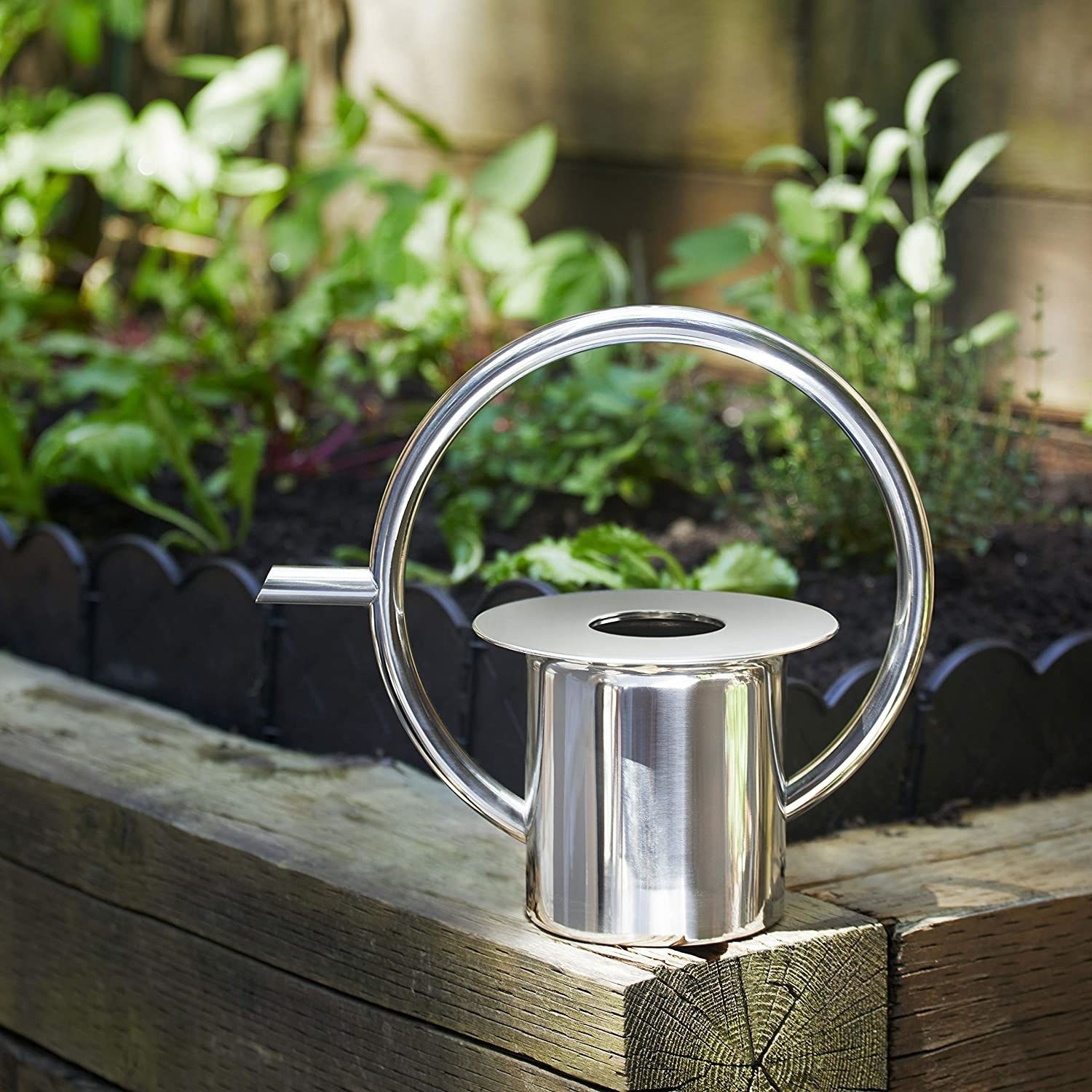 The watering can on the wooden ledge of a garden