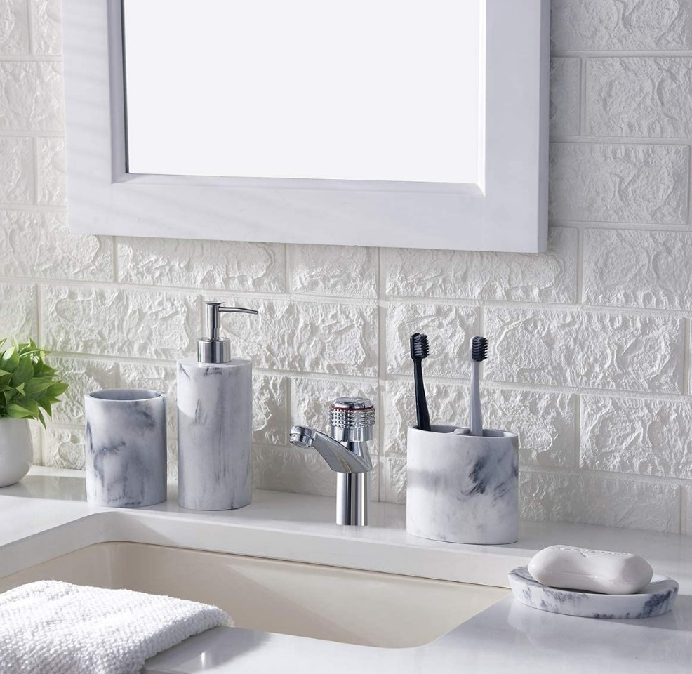 A marble finish soap dispenser, toothbrush holder, cup, and soap holder atop a bathroom vanity