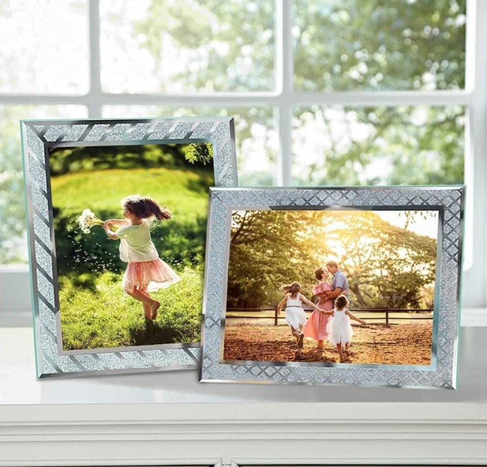 A set of rectangular, glass picture frames atop a windowsill