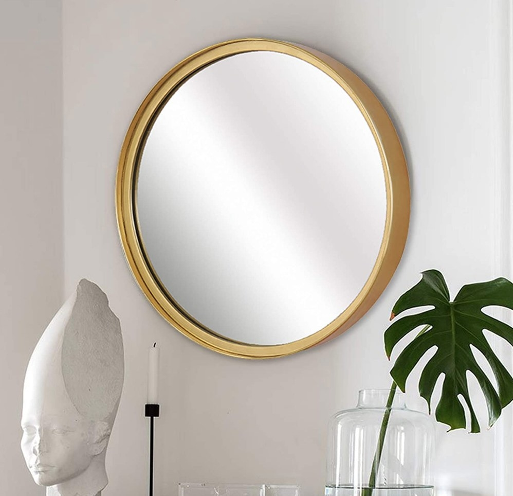 A round mirror with a gold frame mounted on a wall