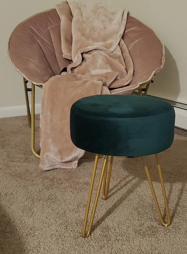 A modern stool with a round dark teal top and gold legs