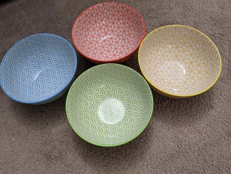 Four small salad bowls with unique patterns in blue, green, red, and yellow