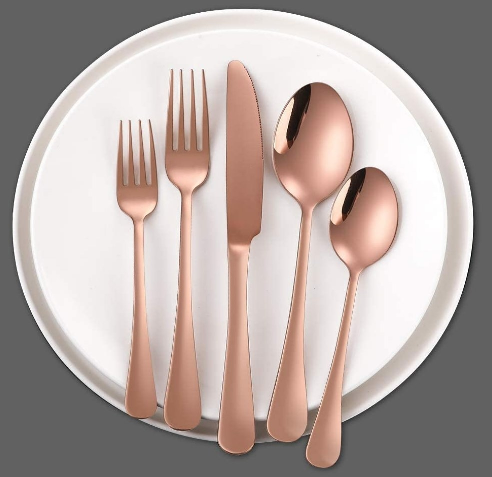 A rose gold silverware set with two spoons, two forks, and one knife atop a plate