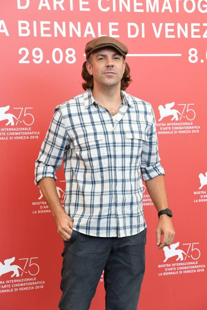 Jason posing on a red carpet in a plaid shirt, slacks, and a newsboy cap