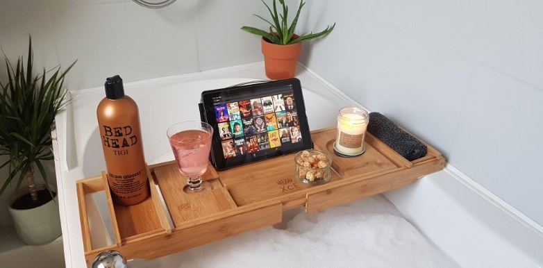 An adjustable, bamboo bath tray above a bath with a drink, iPad, and candle atop