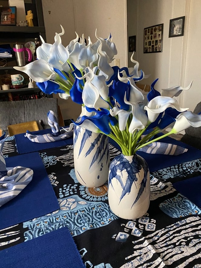 A set of blue/white, mid-century modern ceramic vases filled with flowers