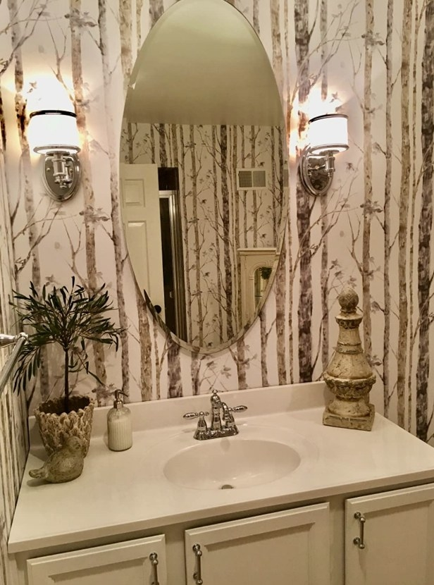 A peel and stick wallpaper with a brown/taupe, birch tree design in a bathroom